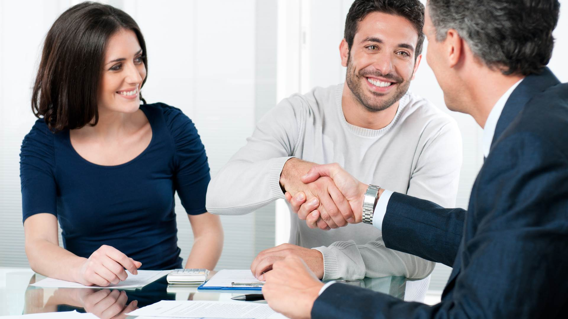 Couple shaking hands with a Loan officer